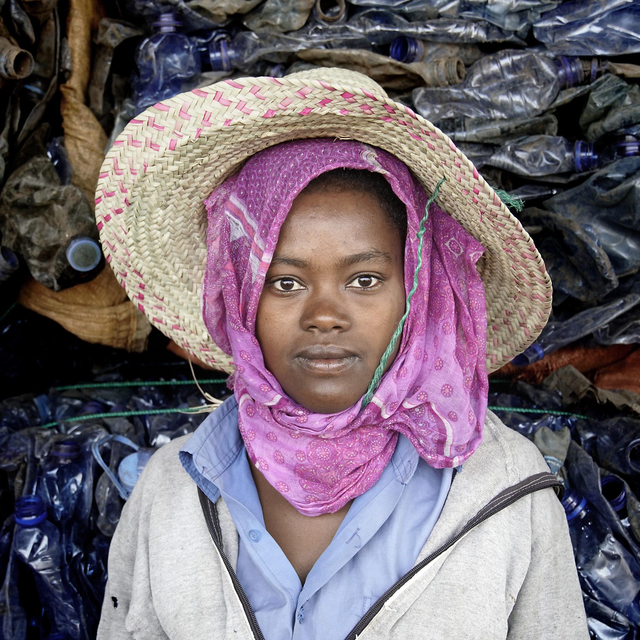 Tumma nuori nainen katsoo kameraan. Muovipulloja näkyy taustalla.
