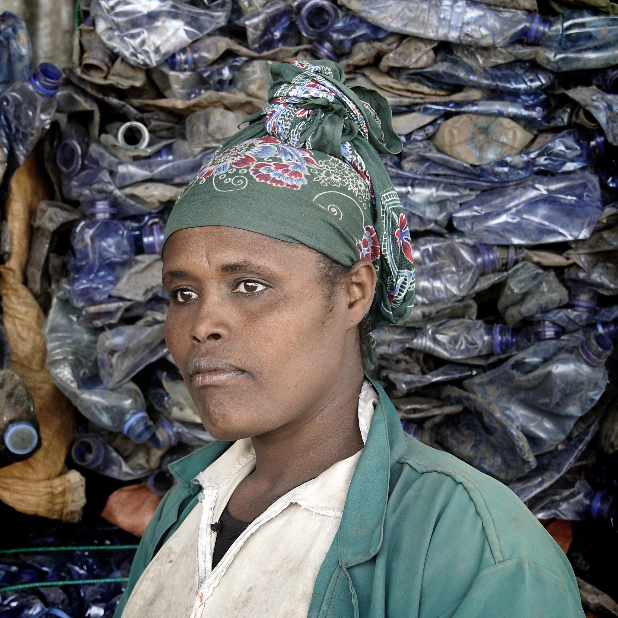 Kuvassa tumma nainen. Muovipulloja näkyy taustalla.