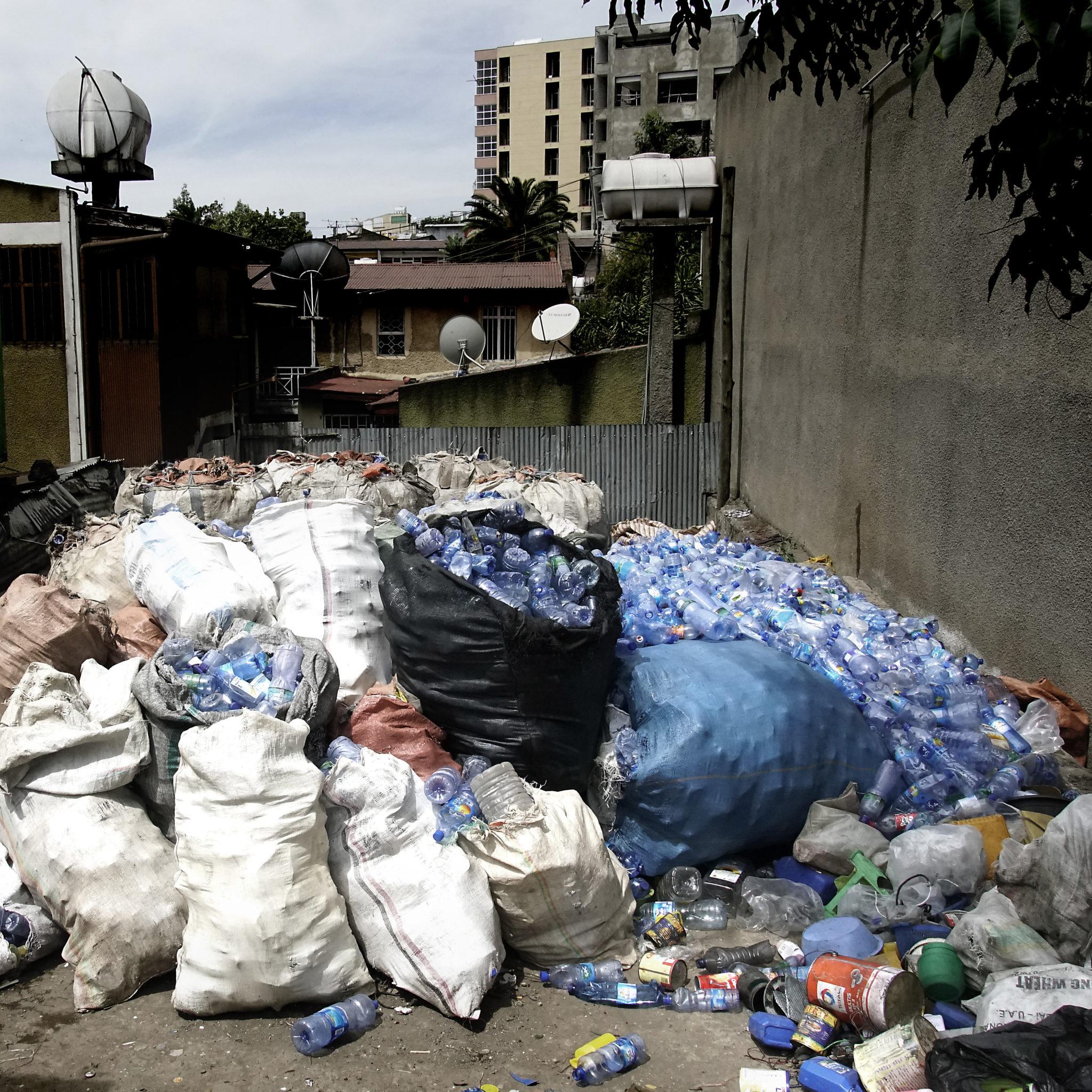 Useita säkillisiä muovipulloja kujalla.