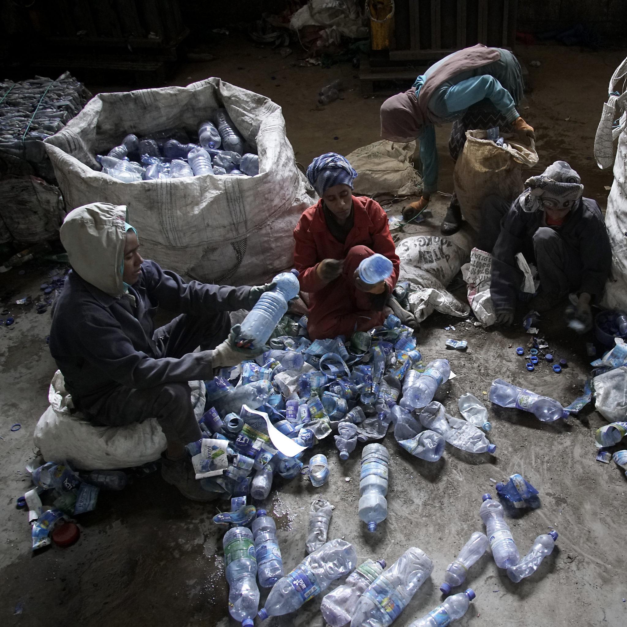 Kolme naista käsittelemässä tyhjiä muovipulloja.