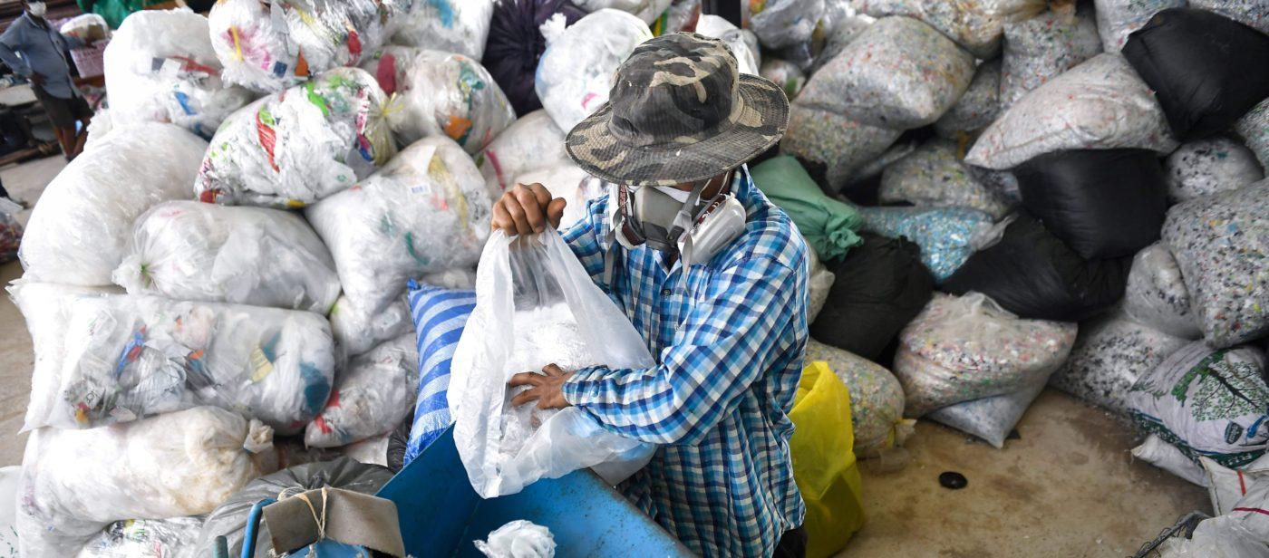 Hengityssuojaimella varustautunut mies purkaa muovikassista muovijätettä koneeseen, joka tekee siitä tienpäällystettä.