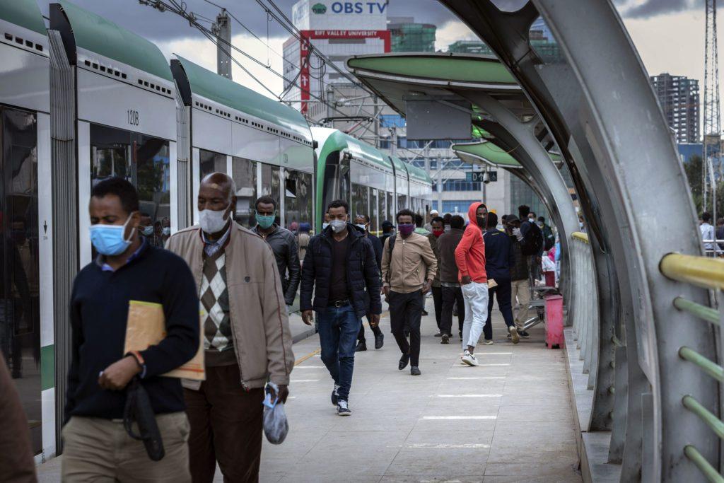 Suojamaskeihin sonnustautuneita miehiä kävelee juna-aseman laiturilla Etiopian pääkaupungissa Addis Abebassa.