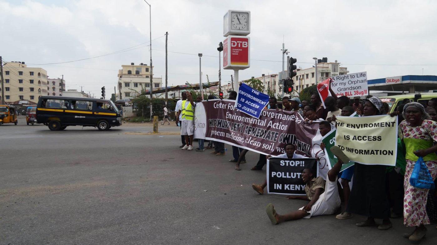 Mielenosoittajat kantavat julisteita kadulla.