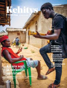 Mies seisoo ja soittaa kitaraa, toinen mies istuu vihreällä muovituolilla ja kuuntelee savitalojen vierustalla.