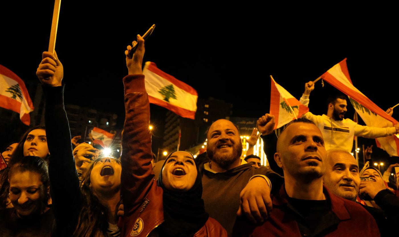 Mielenosoituksessa huutavia ja hymyileviä miehiä ja naisia, taustalla Libanonin punavalkoisia lippuja, joissa keskellä vihreä libanoninsetripuu. Ropande och leende män och kvinnor på en demonstration, i bakgrunden syns Libanons rödvita flaggor med den gröna libanoncedern i mitten.