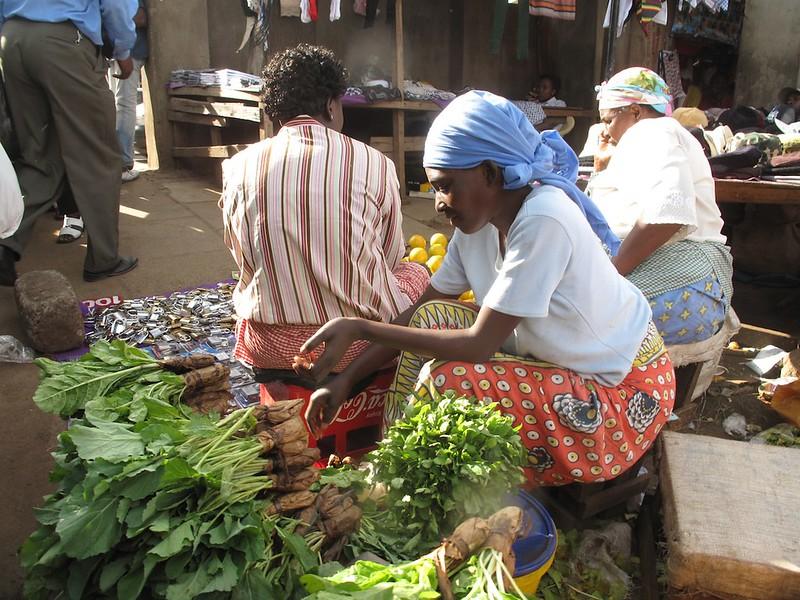 Nainen myy kasviksia torilla.