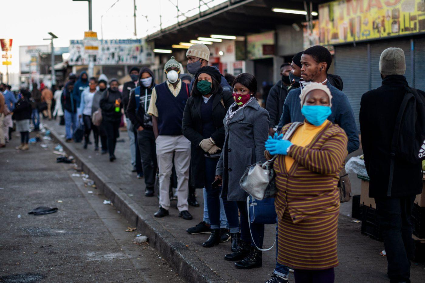 Taksijonossa ihmisiä, joilla maski kasvoillaan.