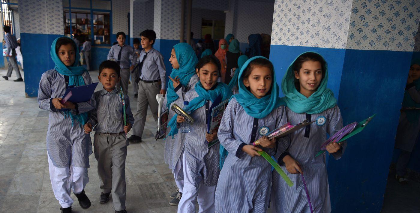 Sinisiin vaatteisiin pukeutuneita koululaisia.