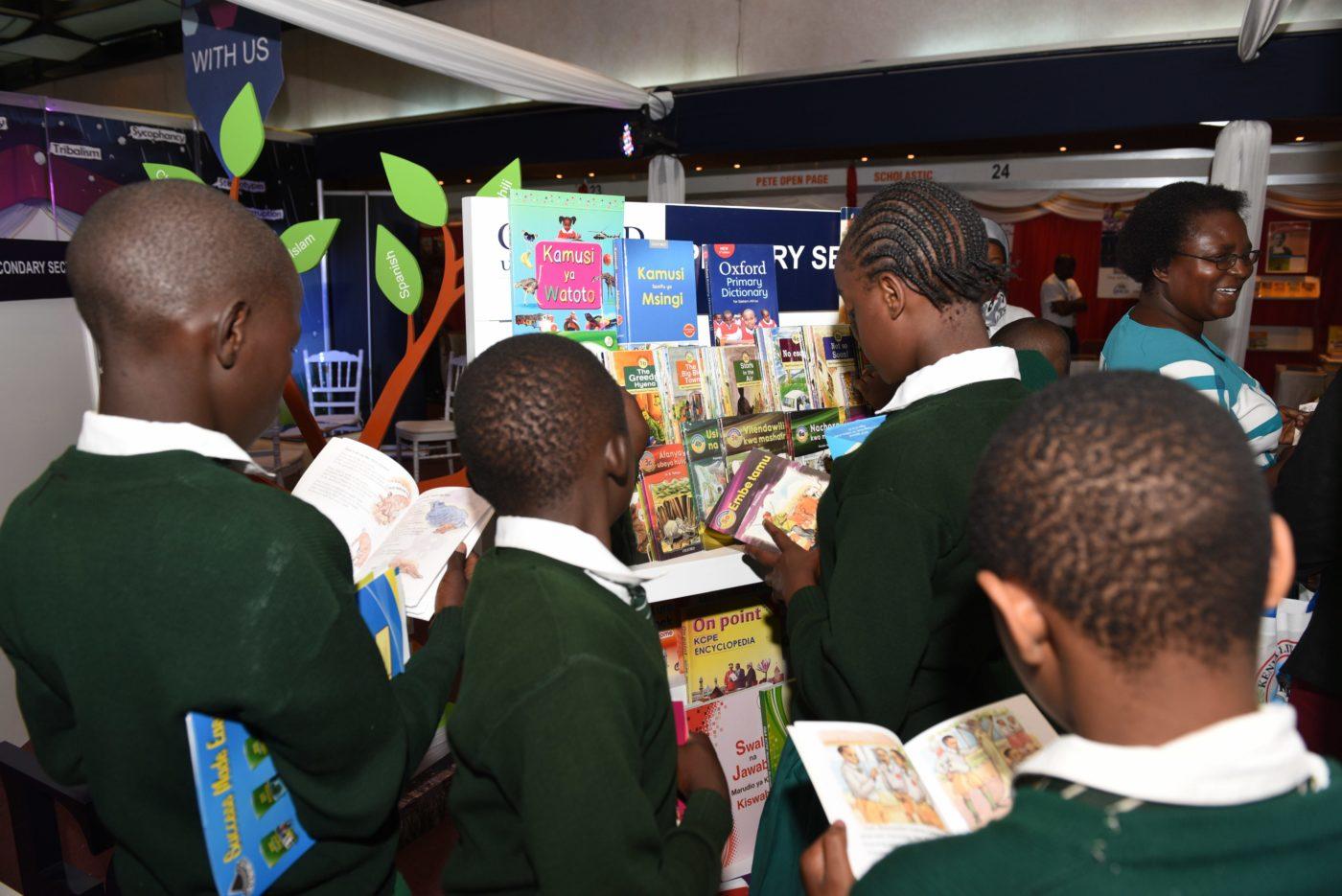 Vihreään koulupukuun puketuneita koululaisia selaamassa kirjoja hyllyn edessä.