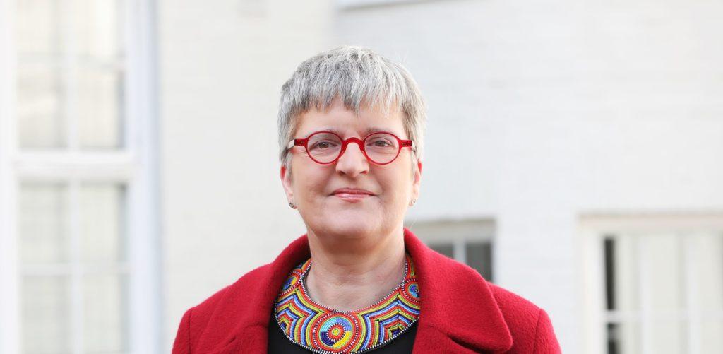 Naisella harmaat lyhyet hiukset, punaiset pyöreät silmälasit ja helmistä punottu värikäs kaulakoru. En kvinna som har grått kort hår, röda runda glasögon och ett färggrant halssmycke av pärlor.