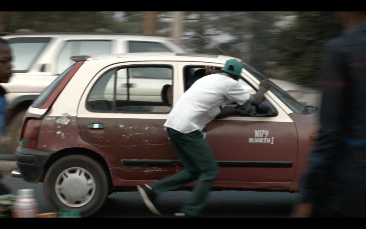 Mies juoksee auton vieressä.