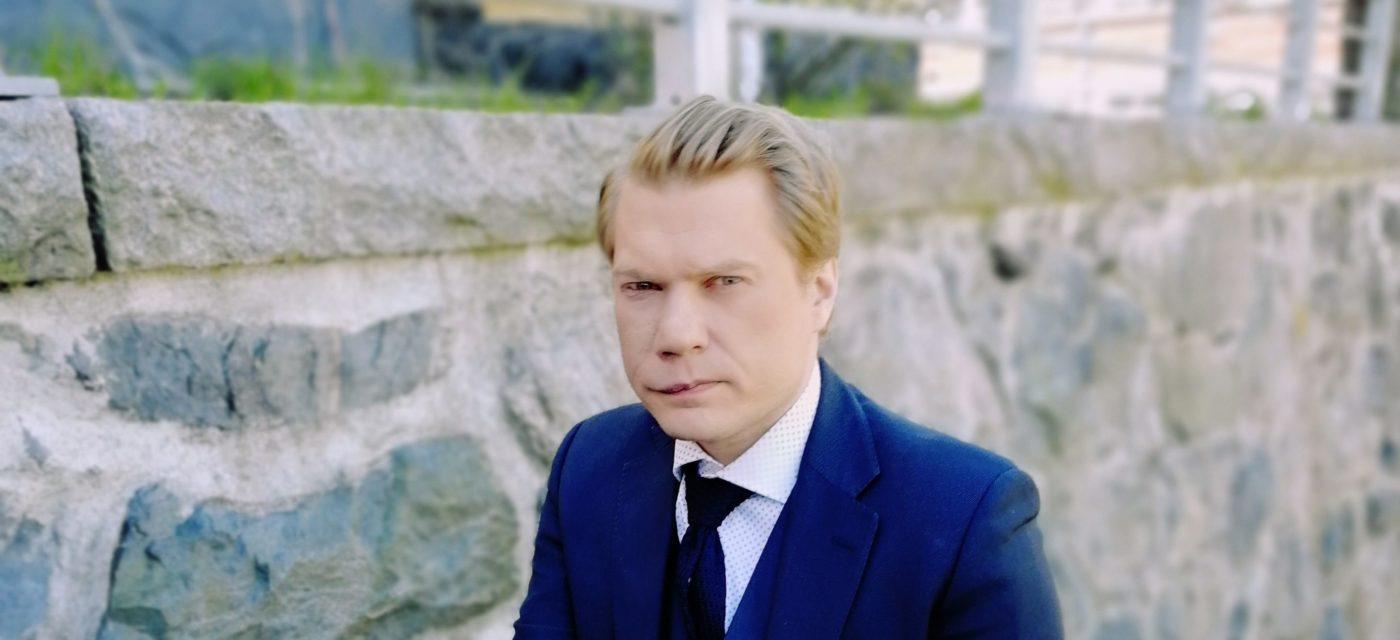 Miehellä vaaleat hiukset, sininen puvuntakki ja musta kravatti.