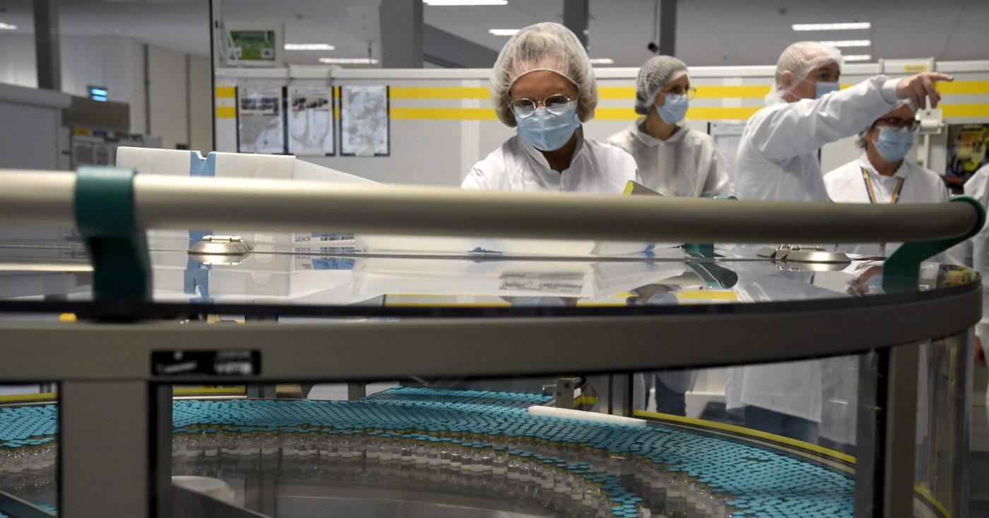 Suojamaskiin sonnustautunut työntekijä ja lasipulloja