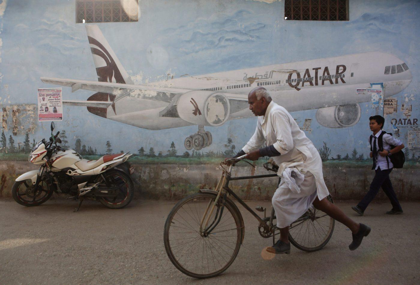 Mies pyöräilee lentokonemainoksen edessä