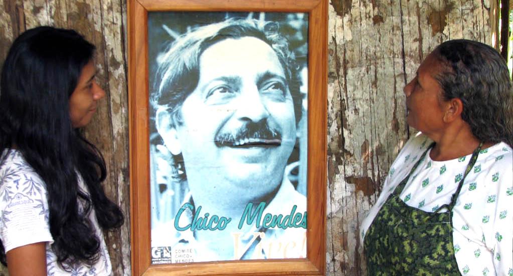 Kaksi naista katsoo aktivisti Chico Mendesin seinällä olevaa kuvaa.