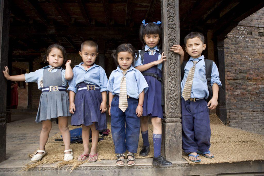 Pieniä koululaisia rivissä sinisissä koulupuvuissa.
