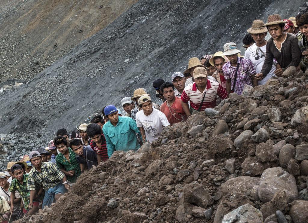 Kaivostyöläisiä rivissä vuorella