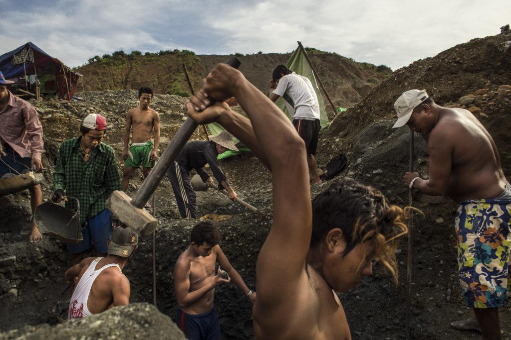 Miehiä kaivamassa hakkuineen