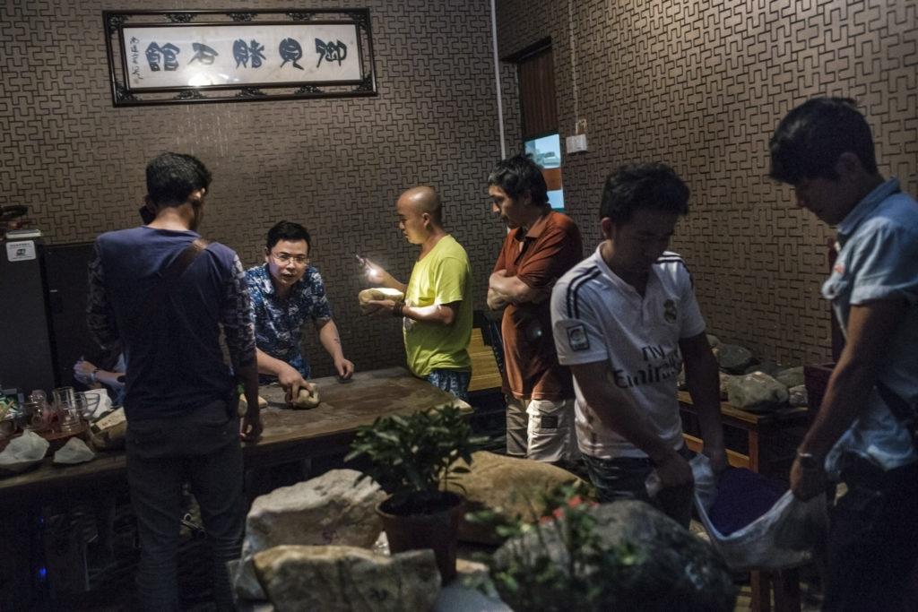 Miehiä tekemässä kauppaa pimeässä huoneessa