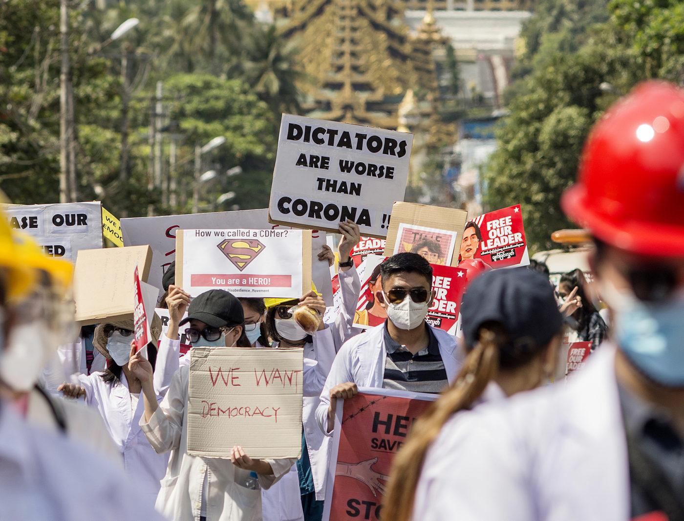 Mielenosoittajia kyltteineen, taustalla kultainen pagoda.
