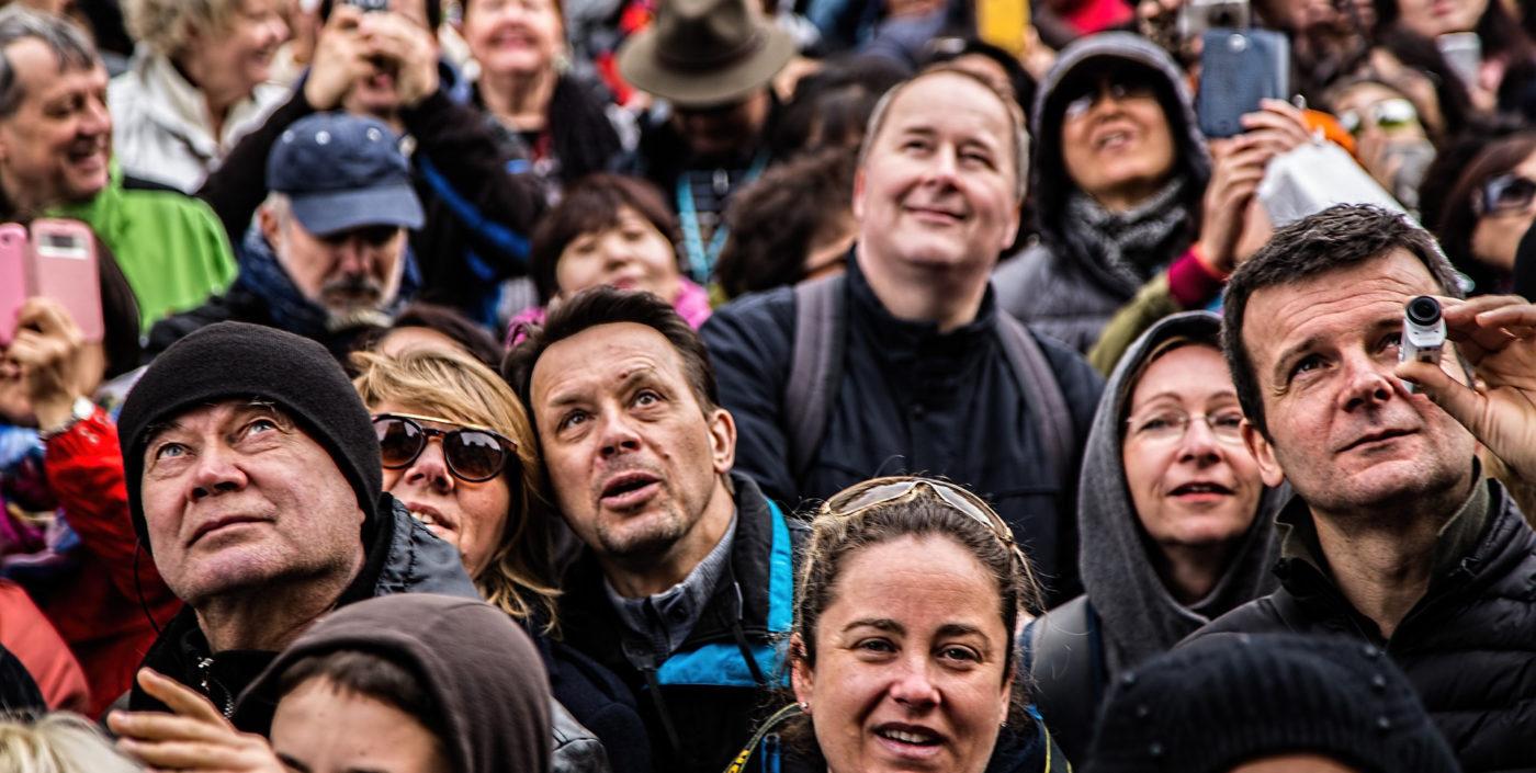 Kuvituskuva, jossa ihmisjoukko katselee ylöspäin, jokaisella eri ilmeet.