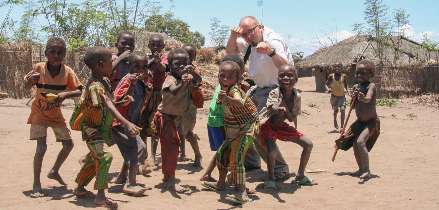 Valkoinen mies poseeraa Mosambikilaislasten kanssa. Kaikilla nyrkit pystyssä kuin karate-leikeissä.