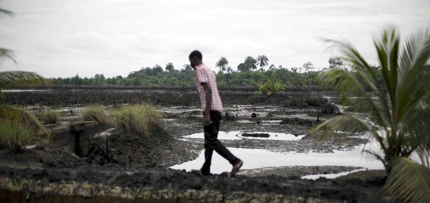 Mies kävelee jokisuistossa, jonka öljyvuodot ovat värjänneet mustaksi.