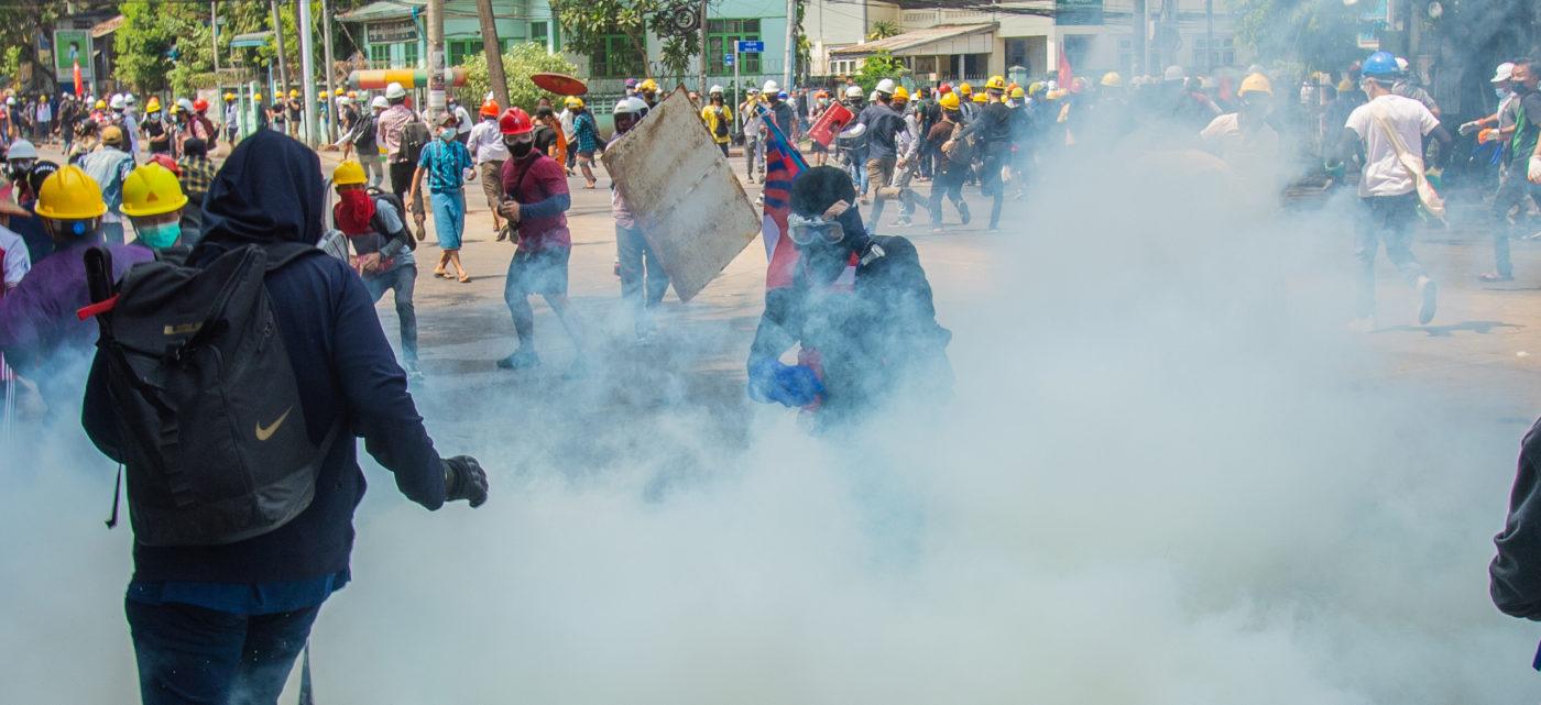 Mielenosoittajat juoksevat karkuun, etualalla poliisi kaasunaamarissa ja iso pilvi kyynelkaasua.