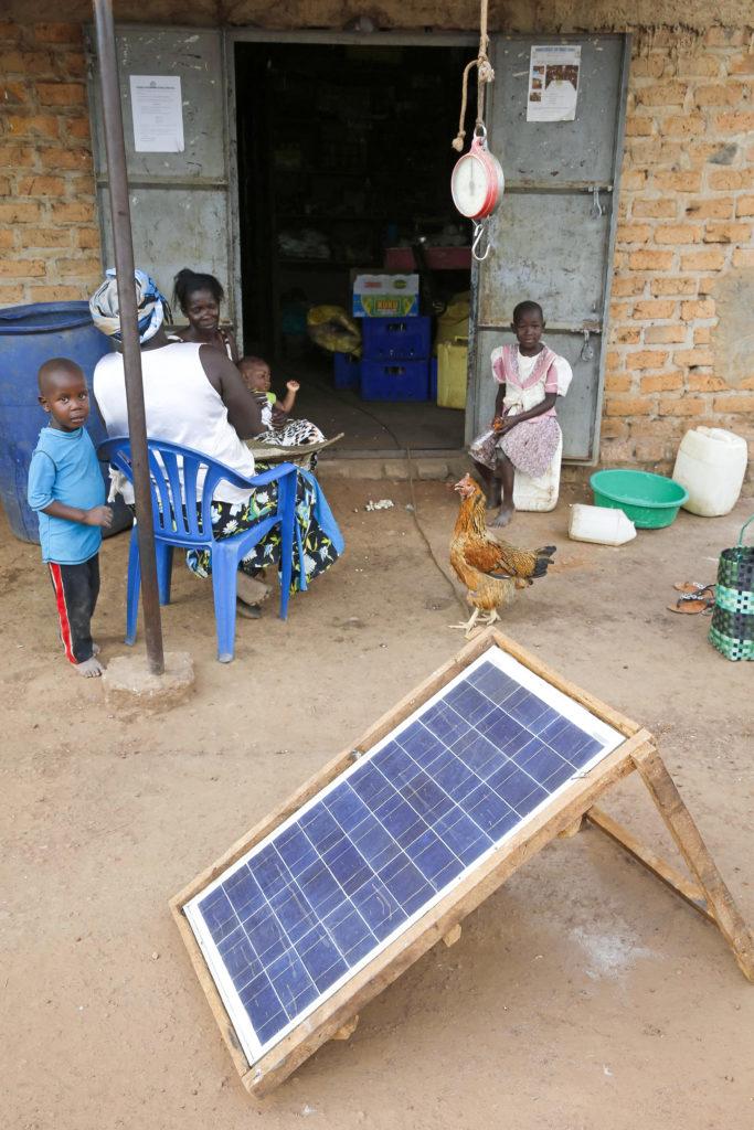 Naisia, lapsia ja aurinkokeräin kyläkaupan edustalla Ugandassa.