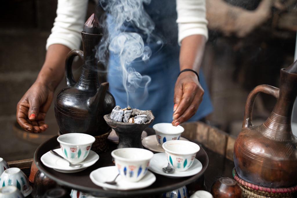Naisen kädet asettelevat tarjottimelle neljää pientä kahvikuppia, joiden vieressä on kaksi kahvipannua ja hiilikeko.