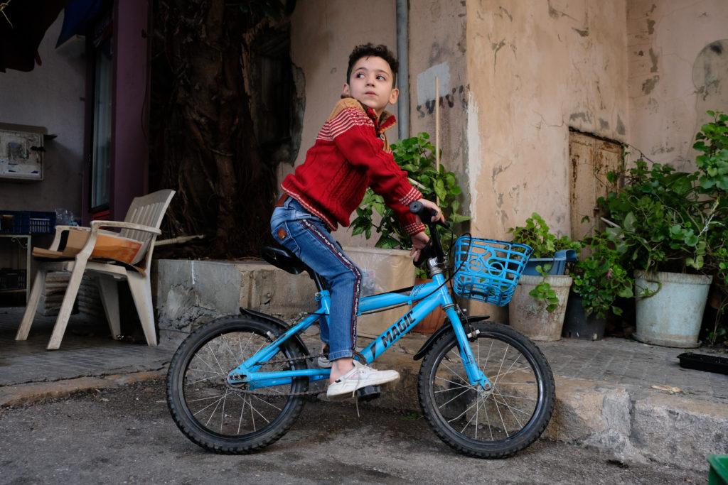 Punaiseen villapaitaan sonnustautunu poika sinisellä polkupyörällä.