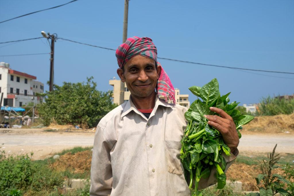 Mies, jolla turbaani päässä ja vihreitä lehtikasveja kädessä.