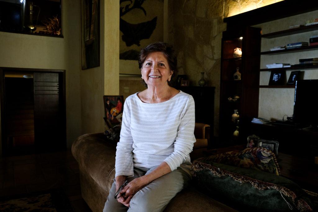 Nainen istuu sohvalla ja katsoo kameraan.