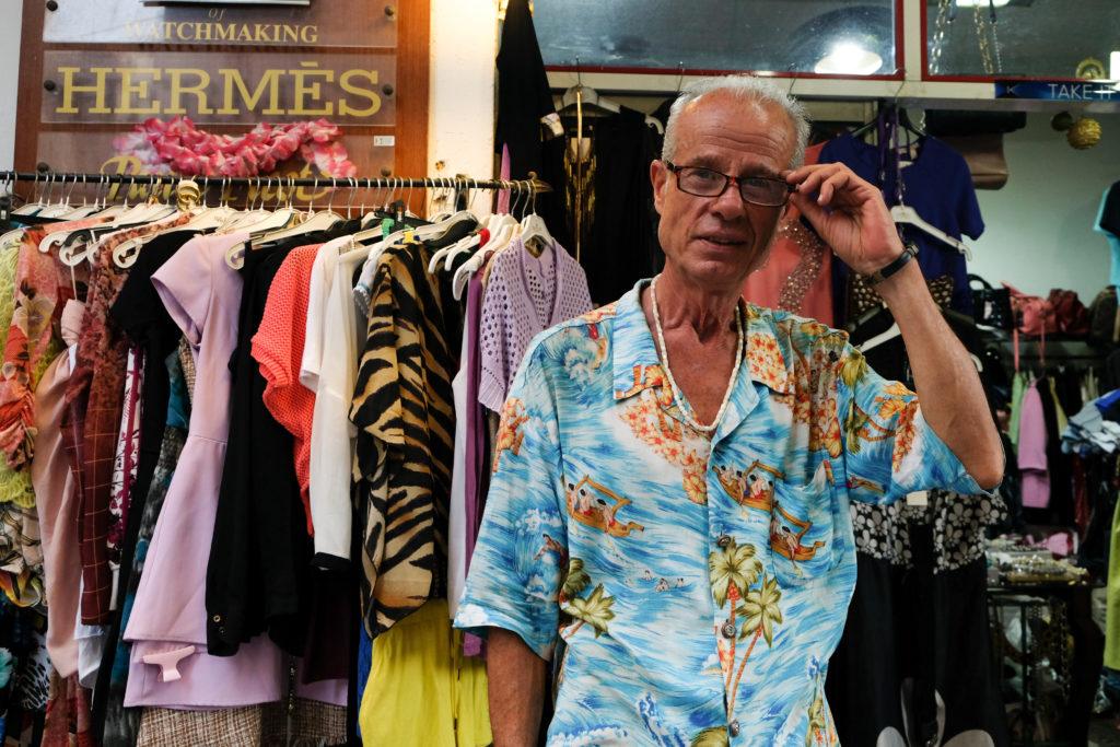 Värikkääseen paitaan pukeutunut mies vaaterekin edessä.