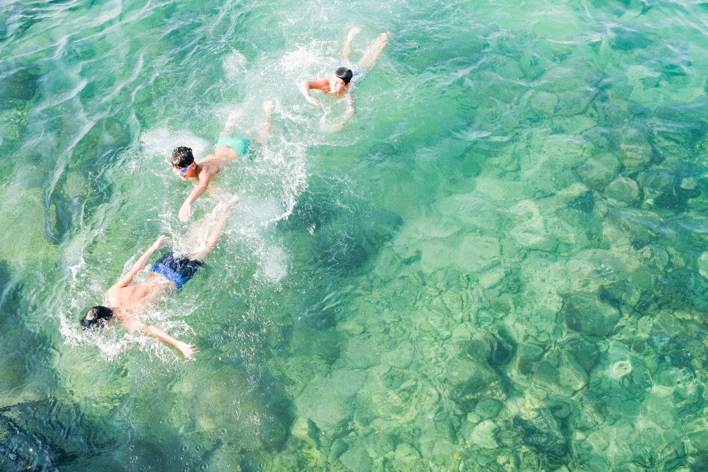 Kolme poikaa ui vihreässä meressä.